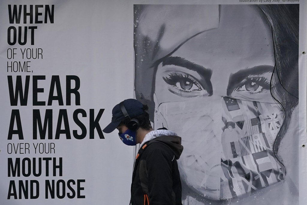 """FILE - In this Saturday, Nov. 21, 2020, file photo, a pedestrian walks past a mural reading: """"When out of your home, Wear a mask over your mouth and n..."""