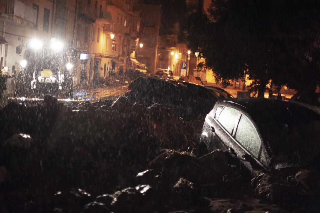 Cars among other debris litter the street in Bitti, Sardinia, Italy, Saturday, Nov. 28, 2020.  The town of Bitti in Sardinia was hit by a storm and fl...