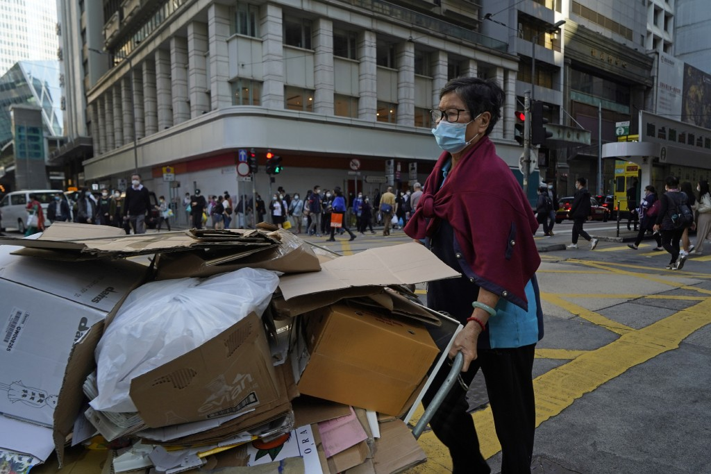 A woman wearing a mask to help protect herself from the coronavirus, pushes a trolley along a street in Hong Kong, Monday, Nov. 30, 2020. (AP Photo/Ki...