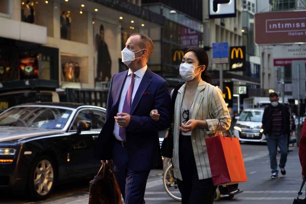 People wearing face masks to protect against the spred of the coronavirus, walk along a street in Hong Kong, Monday, Nov. 30, 2020. (AP Photo/Kin Cheu...