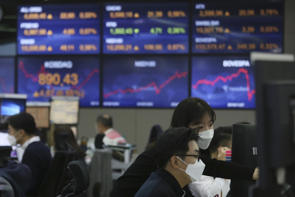 Currency traders watch monitors at the foreign exchange dealing room of the KEB Hana Bank headquarters in Seoul, South Korea, Monday, Nov. 30, 2020. A...