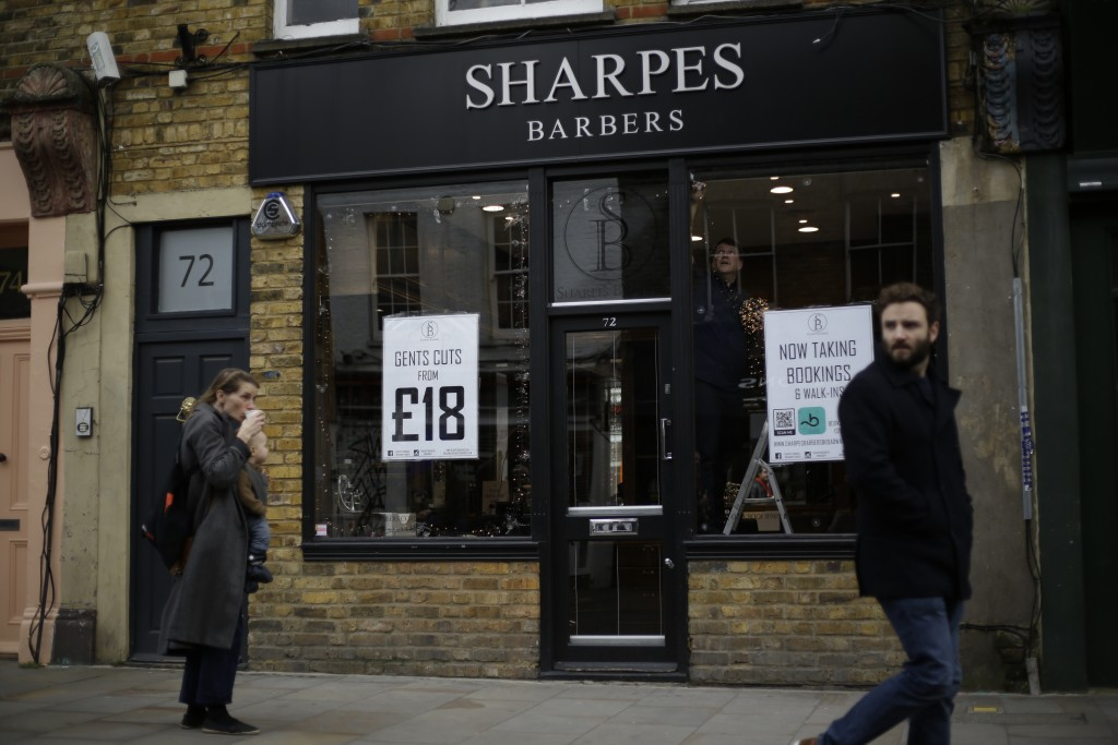 Barber Matthew Jones puts up Christmas lights in the front windows of his 'Sharpes Barbers' in readiness for when England's second coronavirus lockdow...
