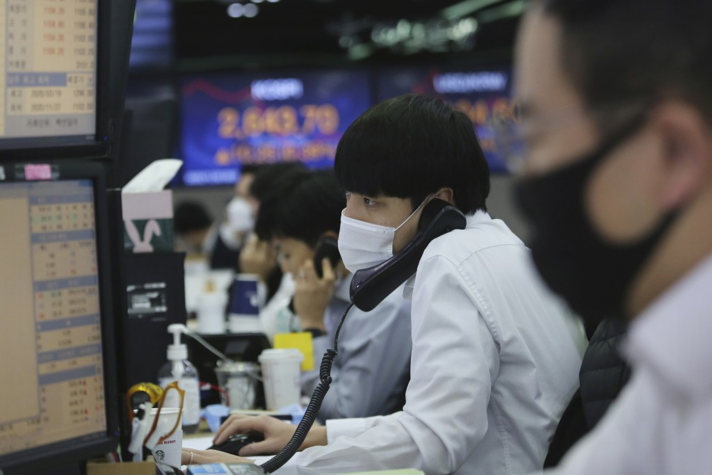 A currency trader watches monitors at the foreign exchange dealing room of the KEB Hana Bank headquarters in Seoul, South Korea, Monday, Nov. 30, 2020...