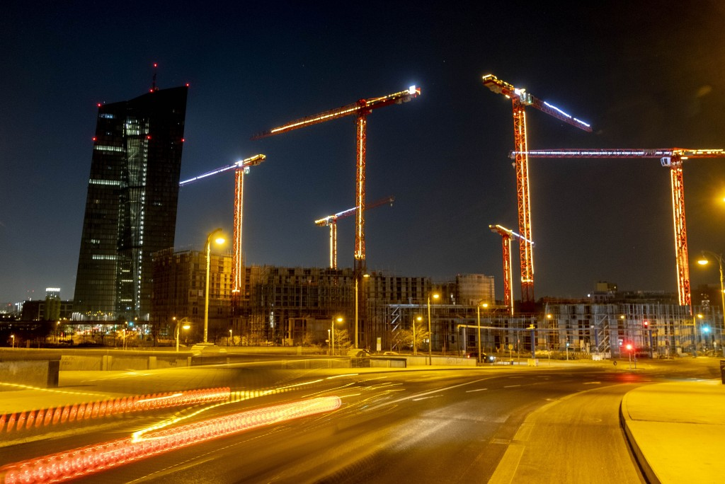 Cranes with Christmas decoration stand next to the European Central Bank, left, in Frankfurt, Germany, Monday, Nov. 30, 2020. (AP Photo/Michael Probst...