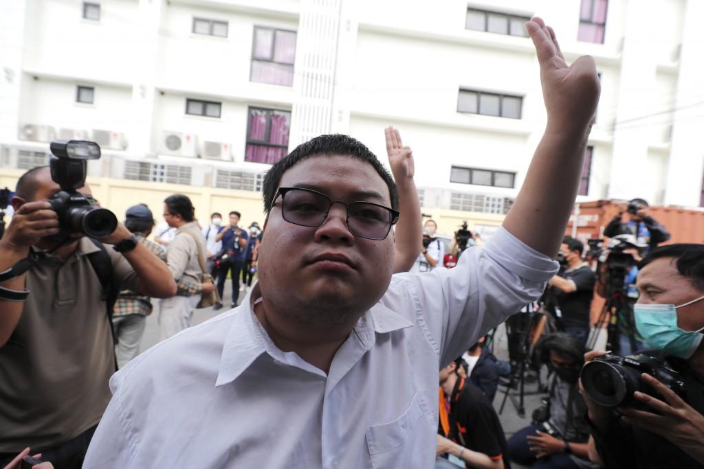 A pro-democracy activist, Parit Chiwarak, raises a three-fingers salute, a symbol of resistance at Chana SongKhram police station in Bangkok, Thailand...