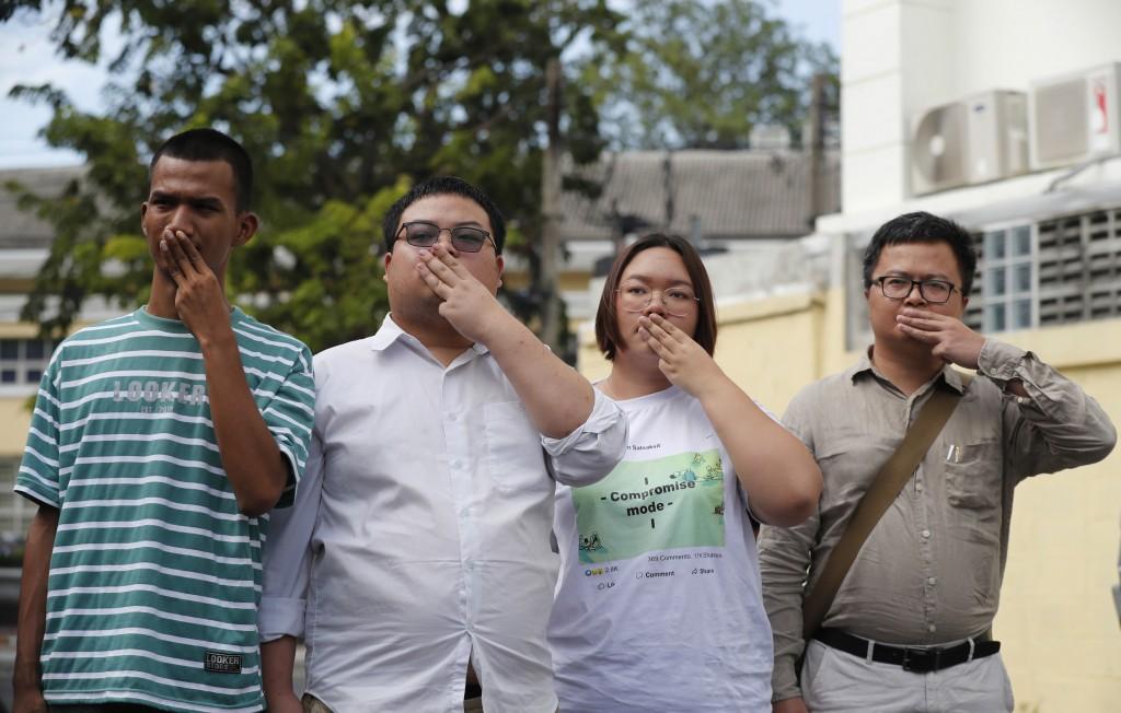 Pro-democracy activists, from left, Panupong Jadnok, Parit Chiwarak, Panusaya Sithijirawattanakul, and Arnon Nampha raise a three-fingers salute, a sy...