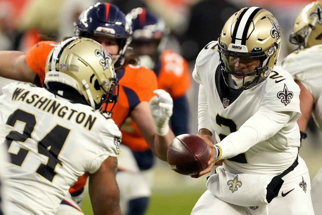 New Orleans Saints quarterback Jameis Winston (2) hands off to running back Dwayne Washington (24) during the second half of an NFL football game agai...