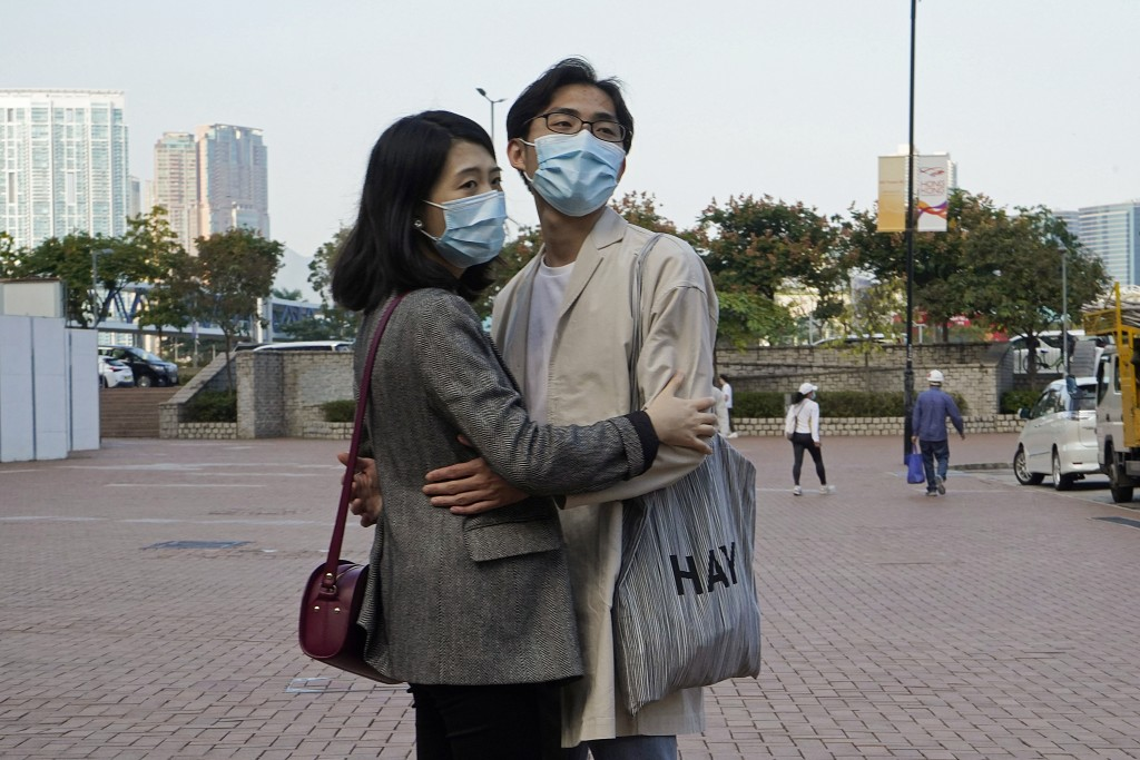 A couple wearing face masks to protect against the coronavirus embrace on a street in Hong Kong, Monday, Nov. 30, 2020. (AP Photo/Kin Cheung)