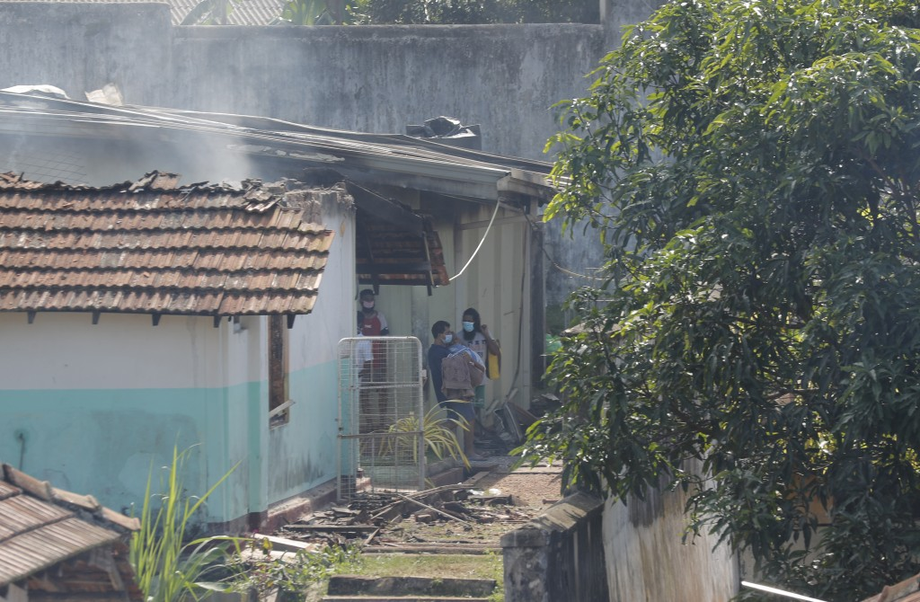 A Sri Lankan inmate of the Mahara prison carries a fellow inmate out from a damaged building as others watch following an overnight unrest in Mahara, ...