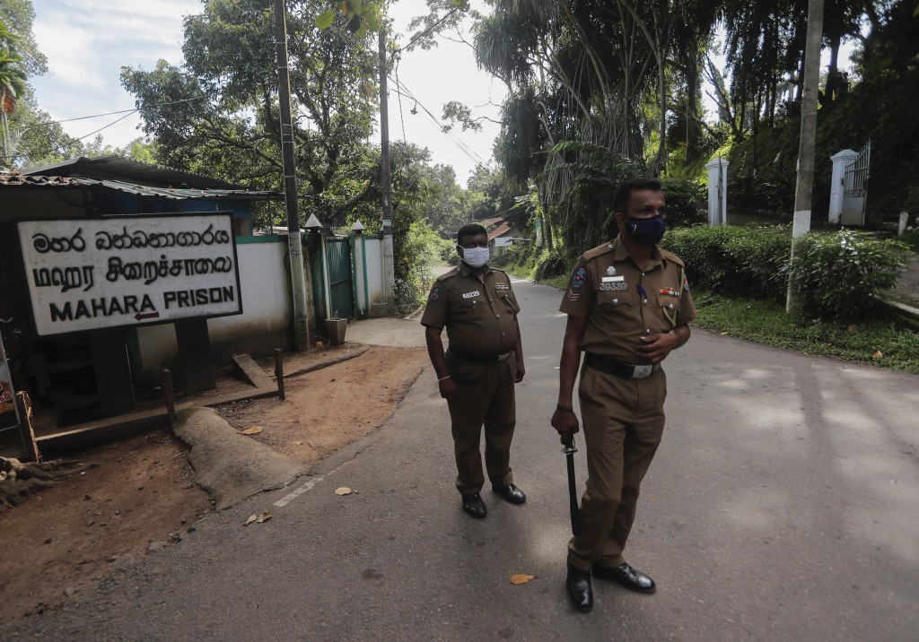 Sri Lankan police officers stand guard at the entrance to the Mahara prison complex following an overnight unrest in Mahara, outskirts of Colombo, Sri...