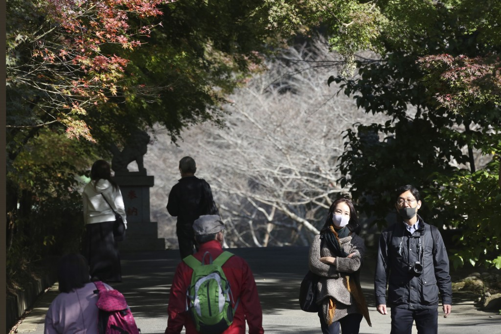 Visitors wearing face masks to protect against the spread of the coronavirus walk through the colorful autumn leaves at the Kenchoji temple in Kamakur...