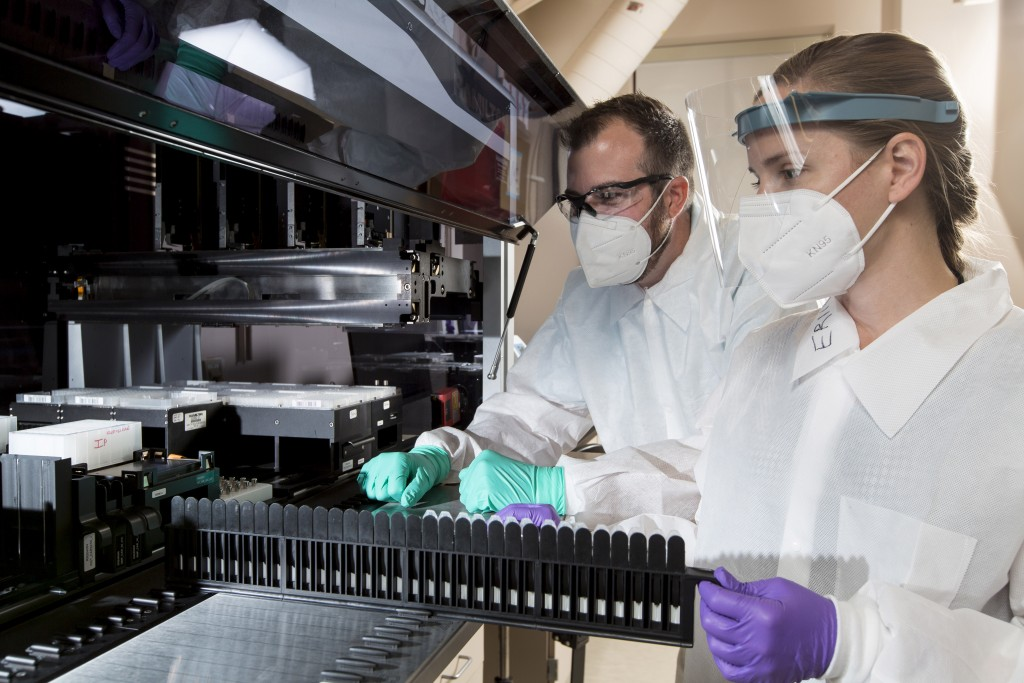 In this Wednesday, July 22, 2020, photo provided by C2N Diagnostics, Matthew Meyer, left, senior proteomics scientist, and Stephanie Knapik, a researc...