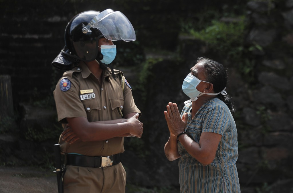 A family member of an inmate pleads to a policeman as she seeks information on the condition of her relative outside the Mahara prison complex followi...