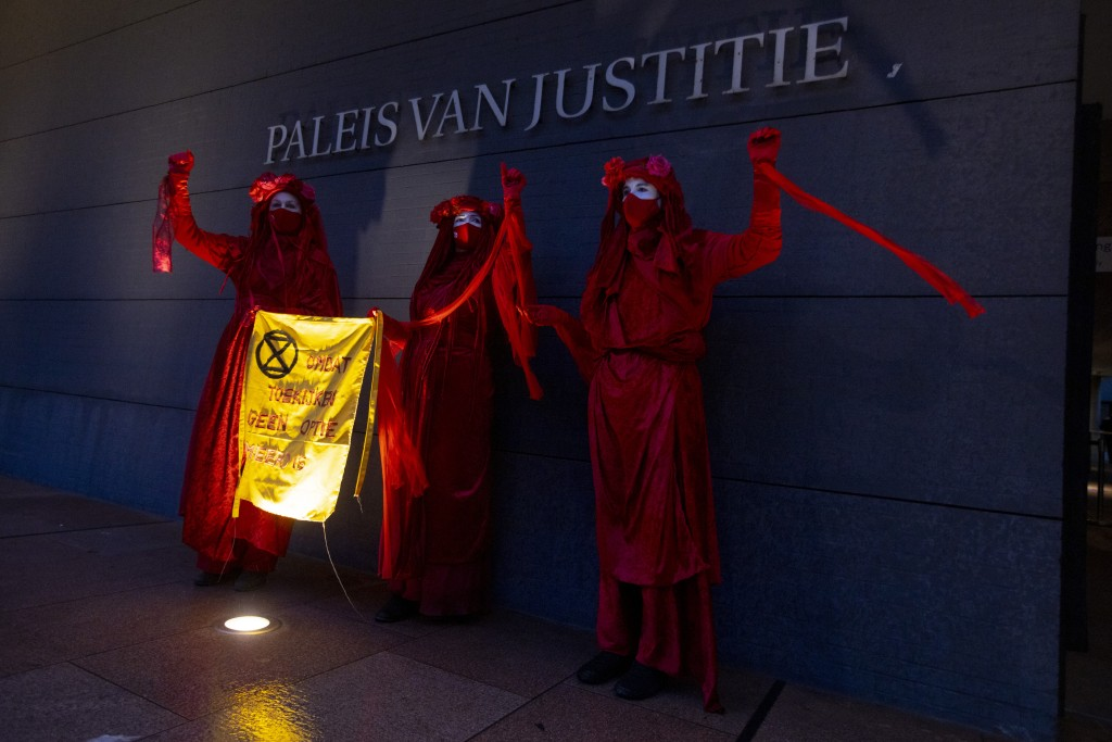 """Demonstrators hold a banner reading """"standing by and watching is no longer an option"""" outside the court building prior to the start of the court case ..."""