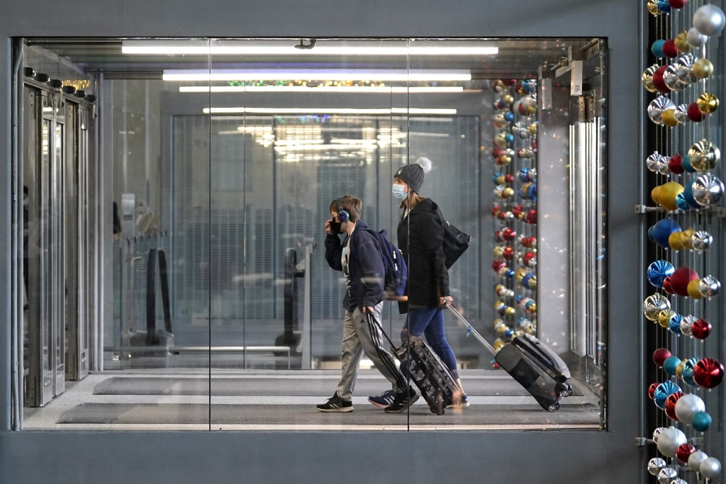FILE - In this Sunday, Nov. 29, 2020 file photo, travelers walk through Terminal 3 at O'Hare International Airport in Chicago. The Transportation Secu...