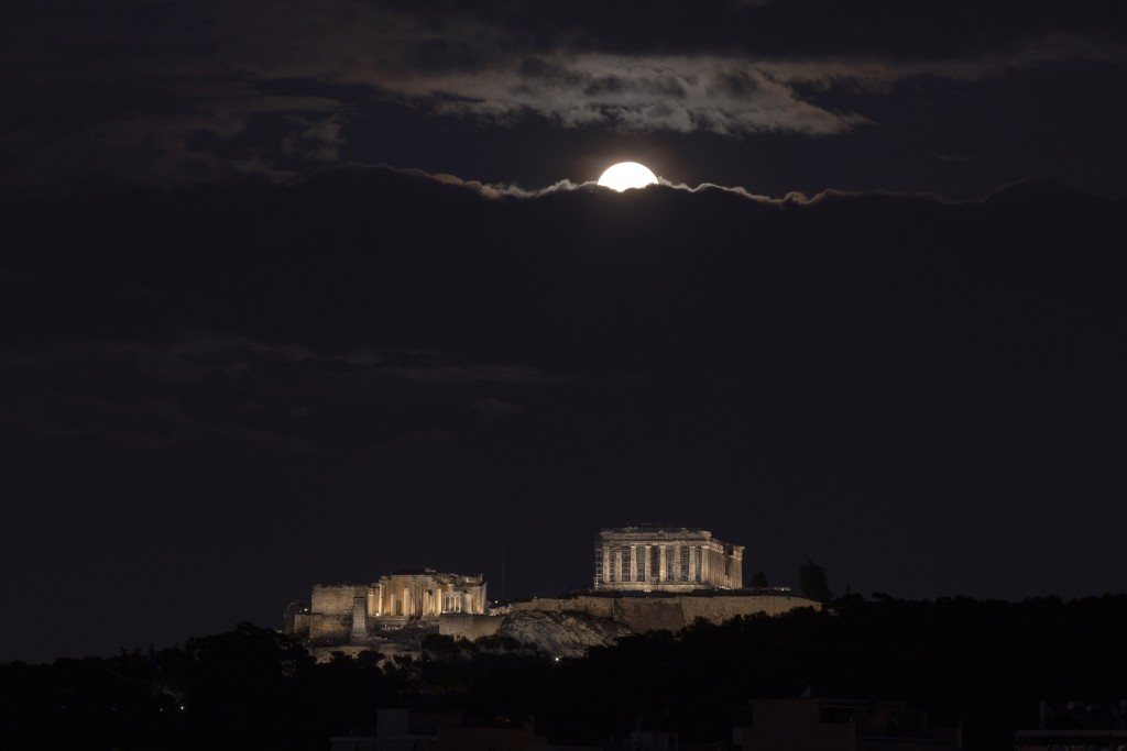 The full moon rises on the Athenian sky above the ancient Acropolis hill during cloudy night , on Monday, Nov. 30, 2020. (AP Photo/Petros Giannakouris...