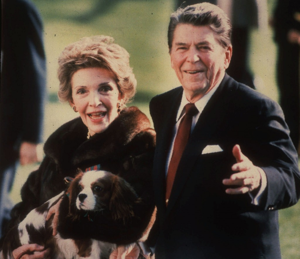 FILE - This December 1986, file photo shows first lady Nancy Reagan holding the Reagans' pet Rex, a King Charles spaniel, as she and President Reagan ...
