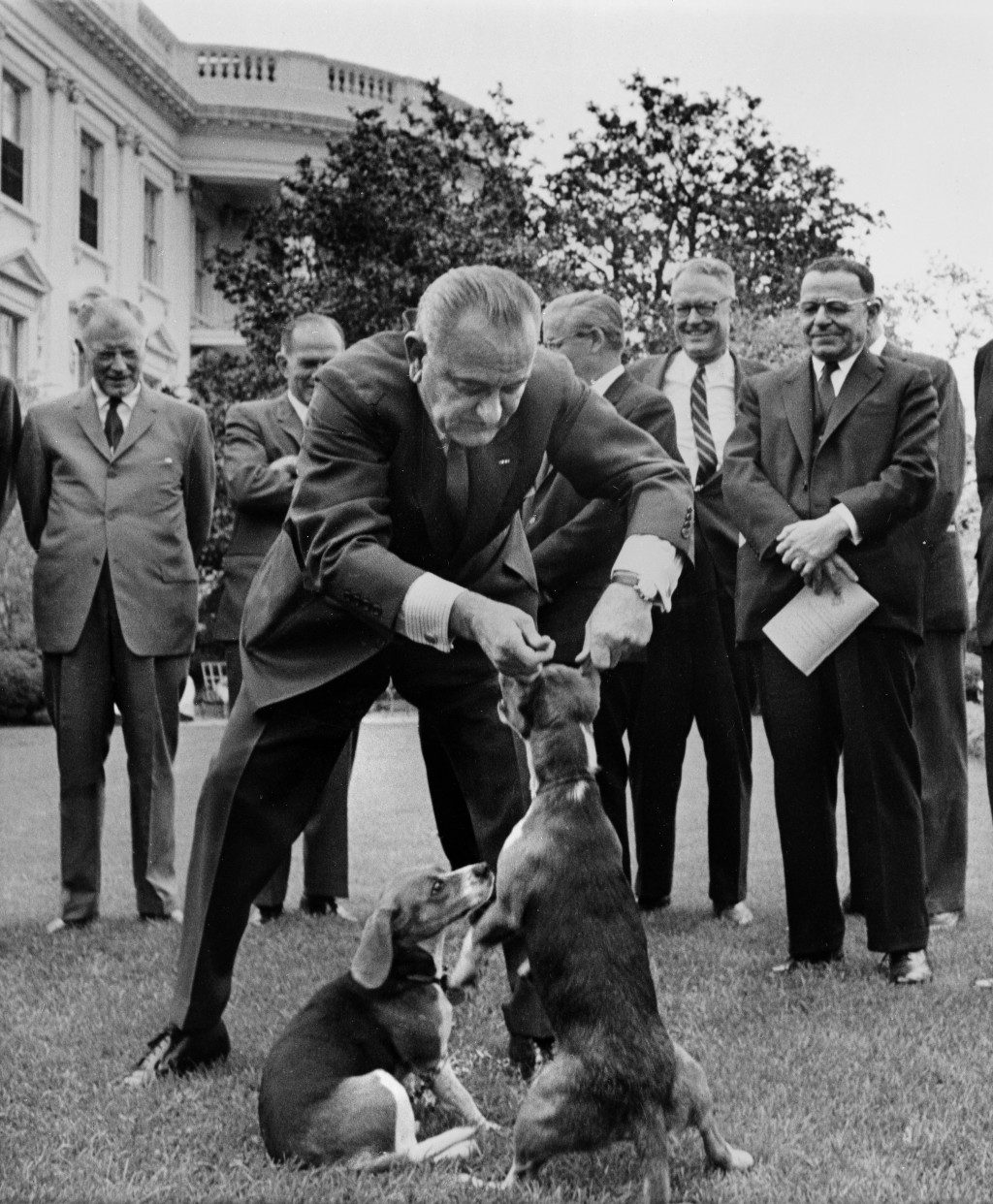 """FILE - In this April 27, 1964, file photo  President Lyndon B. Johnson holds his dog """"Her"""" by the ears as White House visitors look on the White House..."""