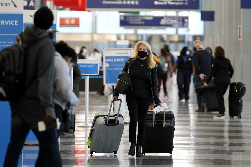 FILE - In this Sunday, Nov. 29, 2020 file photo, a traveler wears a mask as she walks through Terminal 3 at O'Hare International Airport in Chicago. T...