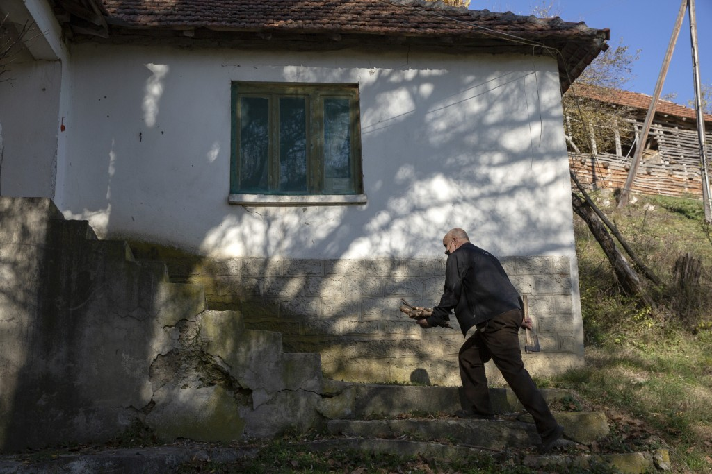 Kosovo Albanian Fadil Rama carries fire wood for a Kosovo Serb Blagica Dicic a lonely 92-year old woman in a remote village of Vaganesh, Kosovo on Thu...