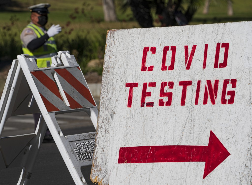 A COVID testing sign directs drivers waiting in line to get a free COVID-19 self-test at Dodger Stadium in Los Angeles, Tuesday, Dec. 1, 2020. Califor...