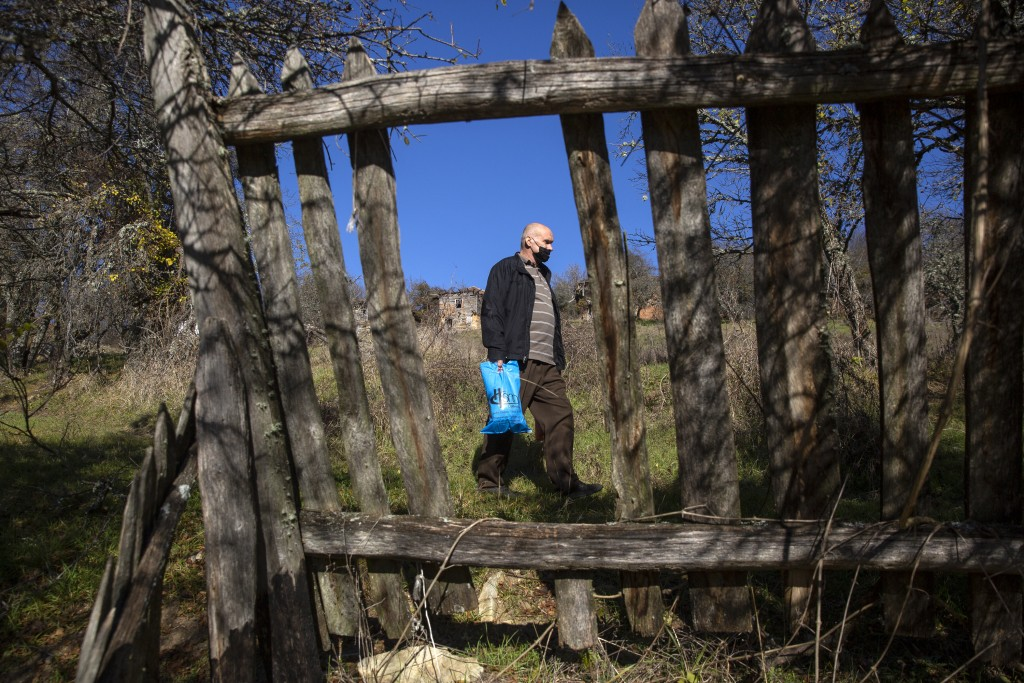 Kosovo Albanian Fadil Rama seen through damaged wooden fence in the deserted village carrying groceries to the only resident Kosovo Serb Blagica Dicic...
