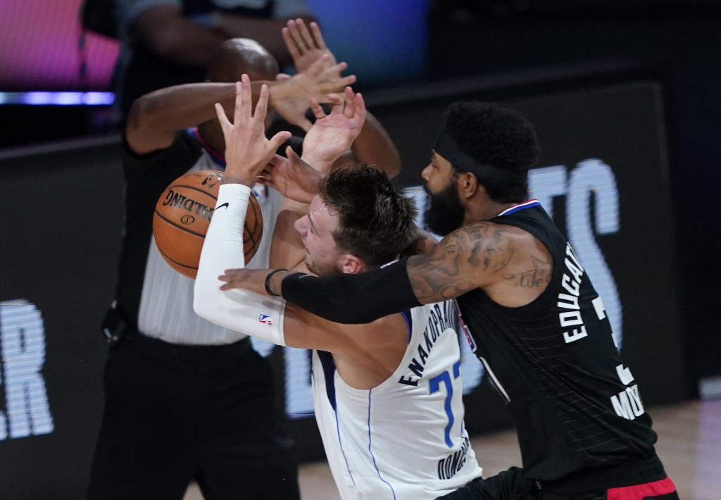FILE - In this Aug. 30, 2020, file photo, Dallas Mavericks' Luka Doncic (77) is fouled by Los Angeles Clippers' Marcus Morris Sr. during the first hal...
