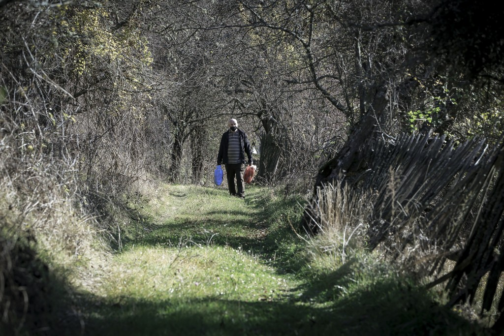 Kosovo Albanian Fadil Rama walking in the deserted village carries groceries to a Kosovo Serb Blagica Dicic a lonely 92-year old woman in a remote vil...