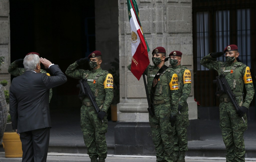 Mexican President Andres Manuel Lopez Obrador salutes the flag during the commemoration of his second anniversary in office, at the National Palace in...