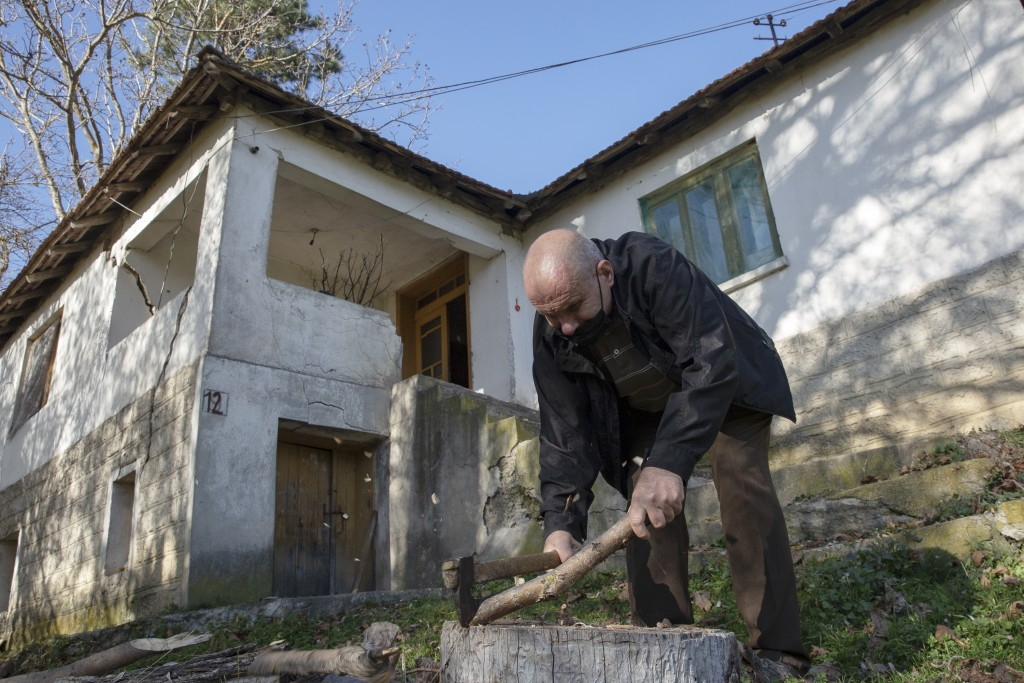 Kosovo Albanian Fadil Rama chops fire wood for a Kosovo Serb Blagica Dicic a lonely 92-year old woman in a remote village of Vaganesh, Kosovo on Thurs...