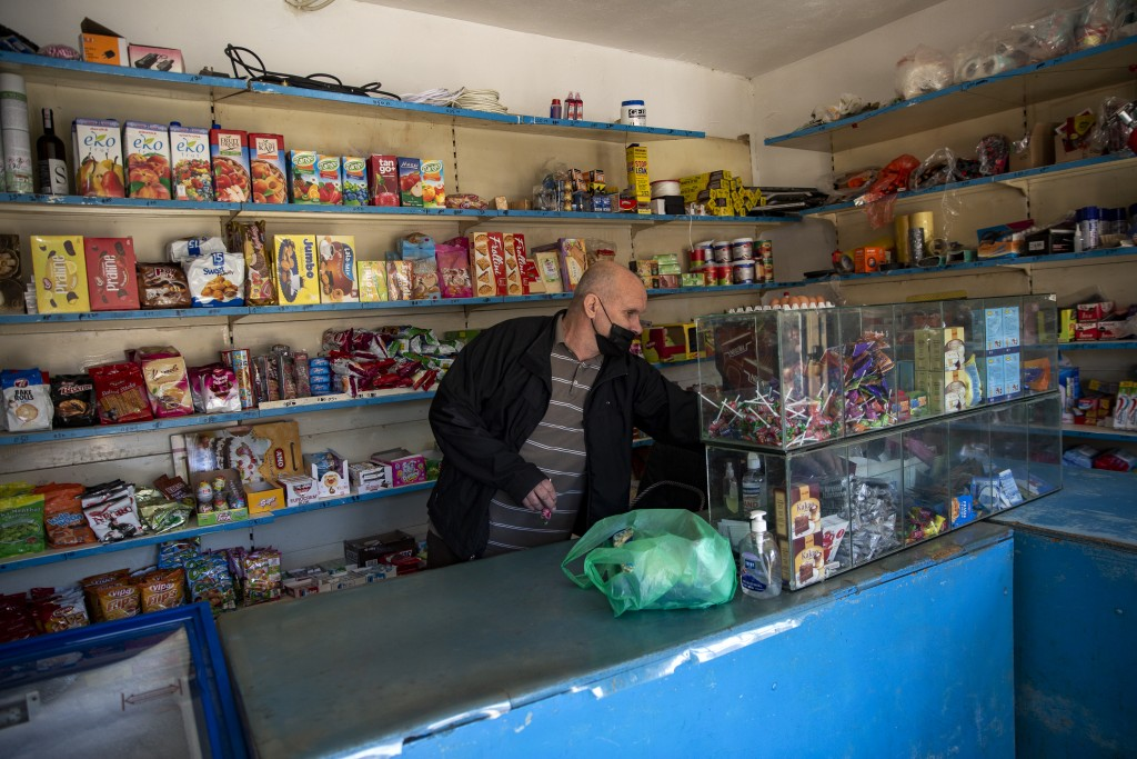 Kosovo Albanian Fadil Rama choses products from his shop to be sent to a Kosovo Serb Blagica Dicic a lonely 92-year old woman in a remote village of V...