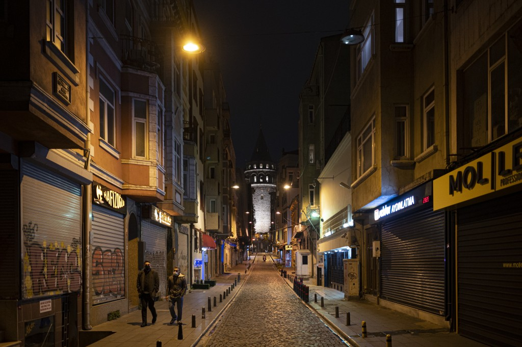People walk in Istanbul, backdropped by the Galata Tower, during a curfew Tuesday, Dec. 1, 2020, part of the new measures to try curb the spread of th...