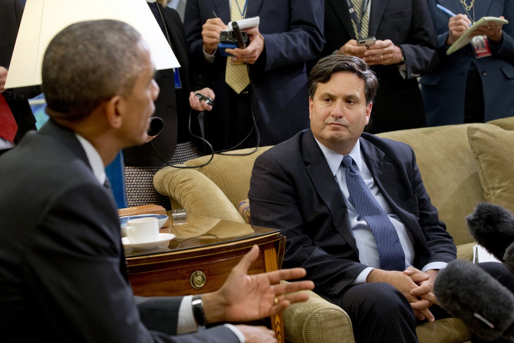 FILE- In this Oct. 22, 2014, file photo, reporters take notes as Ebola coordinator Ron Klain listens to President Barack Obama speak to the media abou...