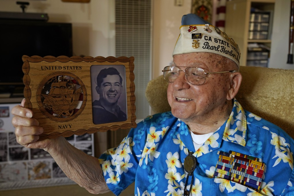 Mickey Ganitch, a survivor of the 1941 attack on Pearl Harbor, holds a plaque with a picture of himself as a young sailor, while sitting in the living...