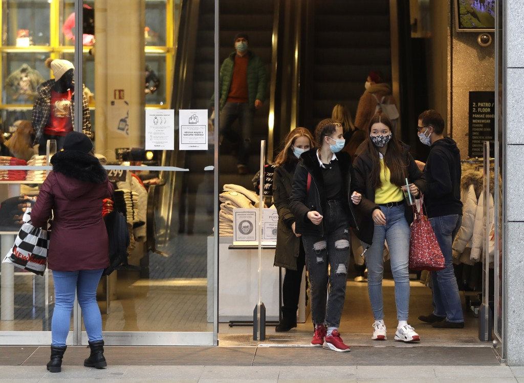 People leave a store in Prague, Czech Republic, Thursday, Dec. 3, 2020. A sign of normalcy has returned to the Czech Republic ahead of the Christmas p...