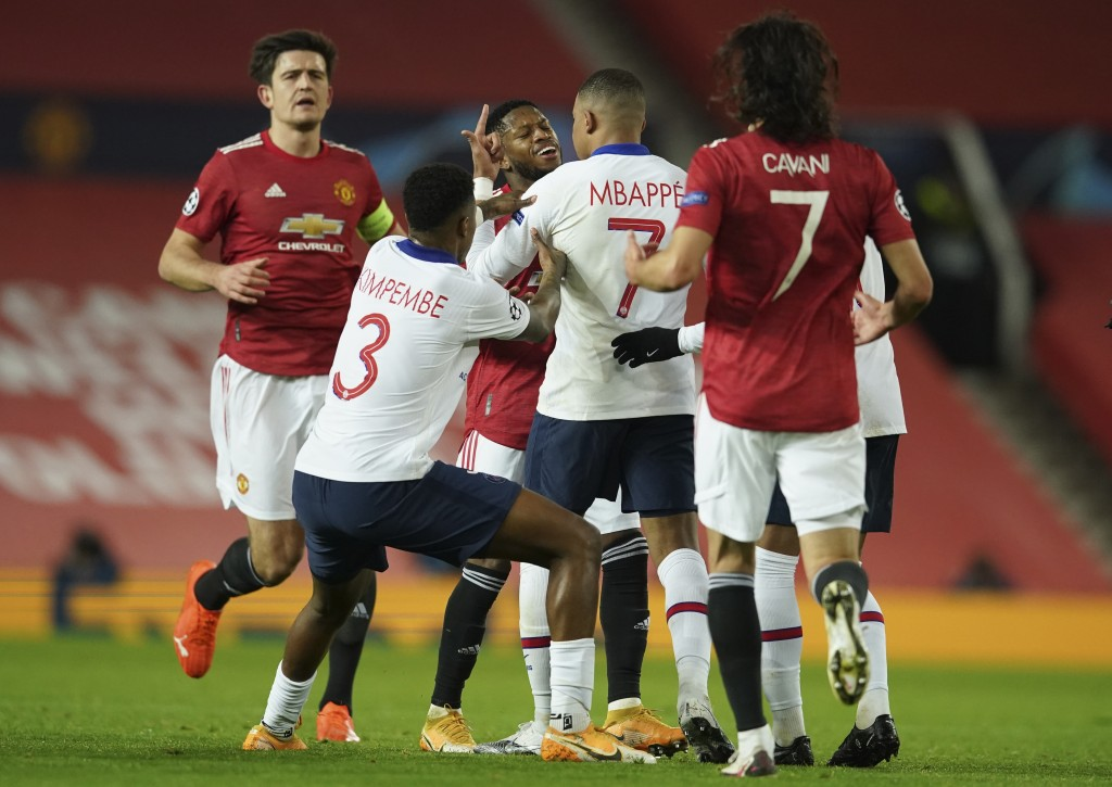 Manchester United's Fred, centre is confronted by PSG players after an incident off the ball during a Group H Champions League soccer match between Ma...