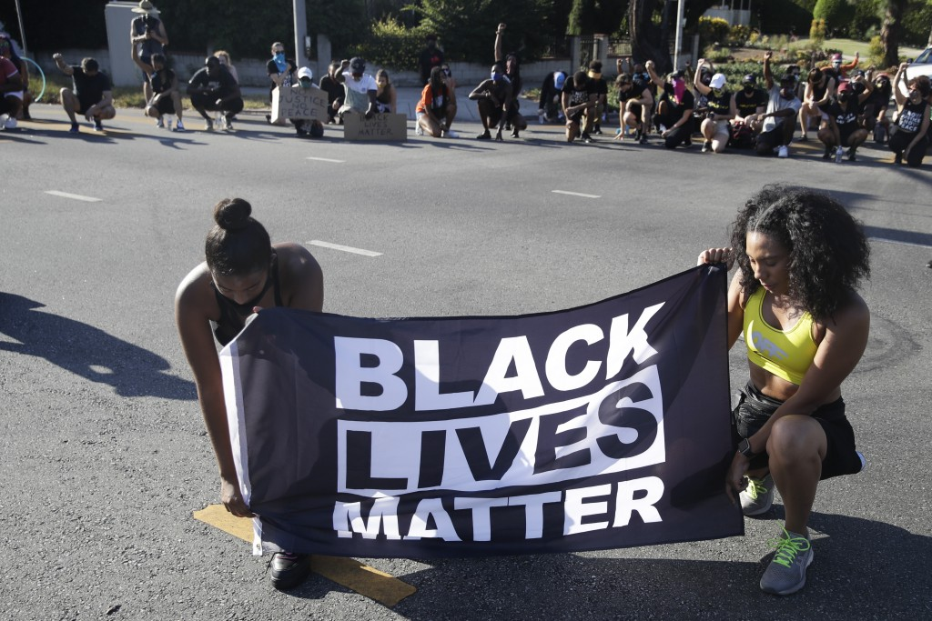FILE - In this July 11, 2020 file photo, Alycia Pascual-Pena, left, and Marley Ralph kneel while holding a Black Lives Matter banner during a protest ...