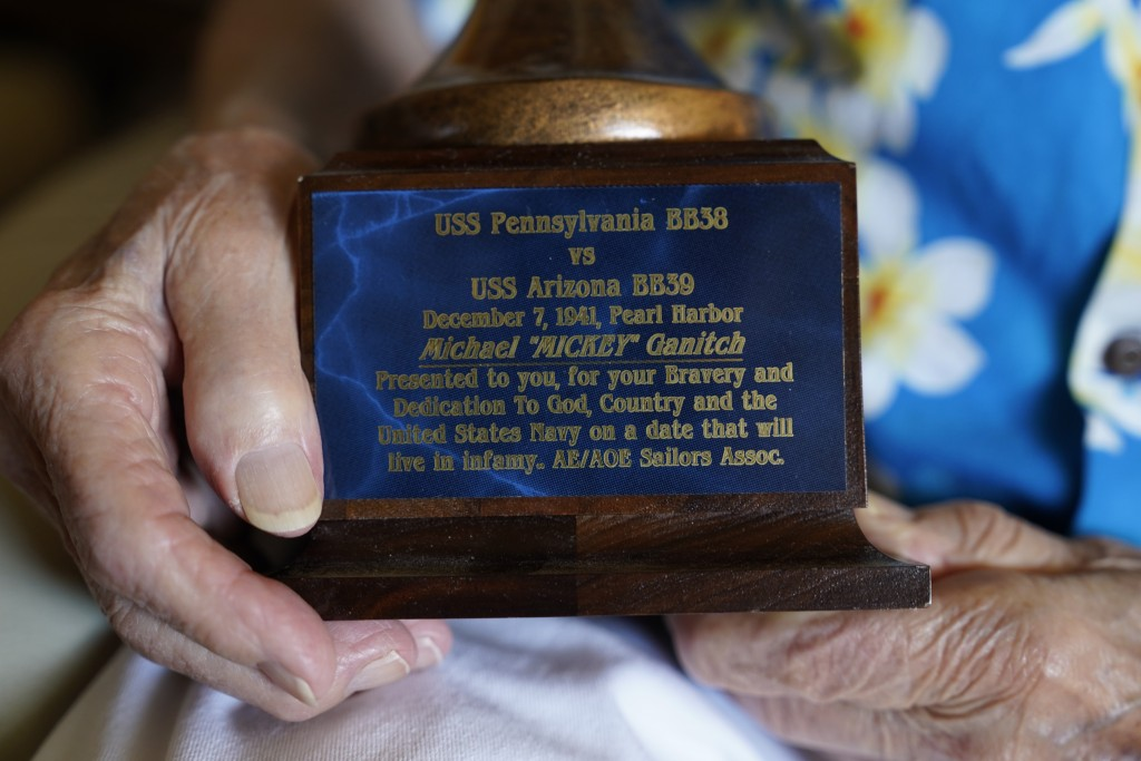 Mickey Ganitch, a 101-year-old survivor of the attack on Pearl Harbor, holds the base of a football statue he was given, in the living room of his hom...