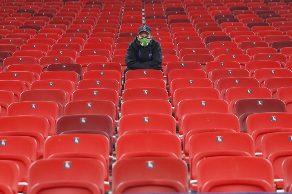 A technical staff sits on empty stands ahead of the Champions League group G soccer match between Ferencvaros and Barcelona at the Ferenc Puskas stadi...