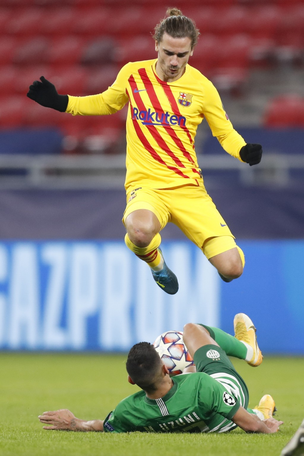Barcelona's Antoine Griezmann is tackled by Ferencvaros' Myrto Uzuni during the Champions League group G soccer match between Ferencvaros and Barcelon...