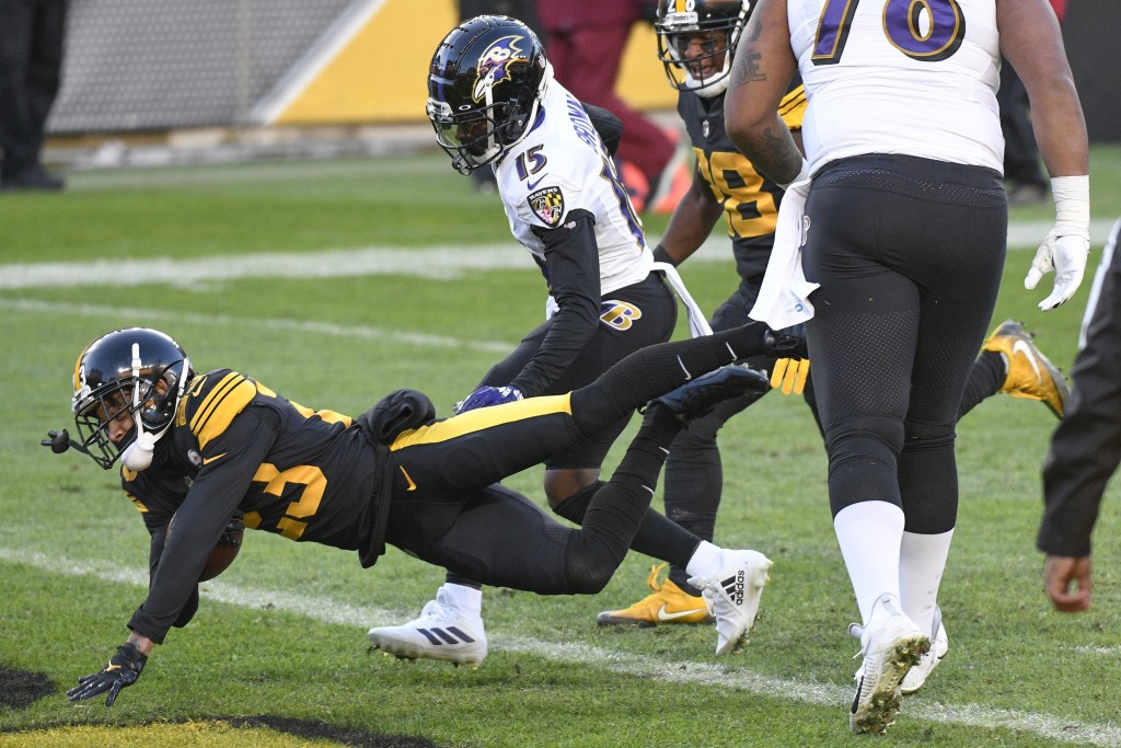 Pittsburgh Steelers cornerback Joe Haden (23) dives into the end zone in front \of Baltimore Ravens wide receiver Marquise Brown (15) with a touchdown...
