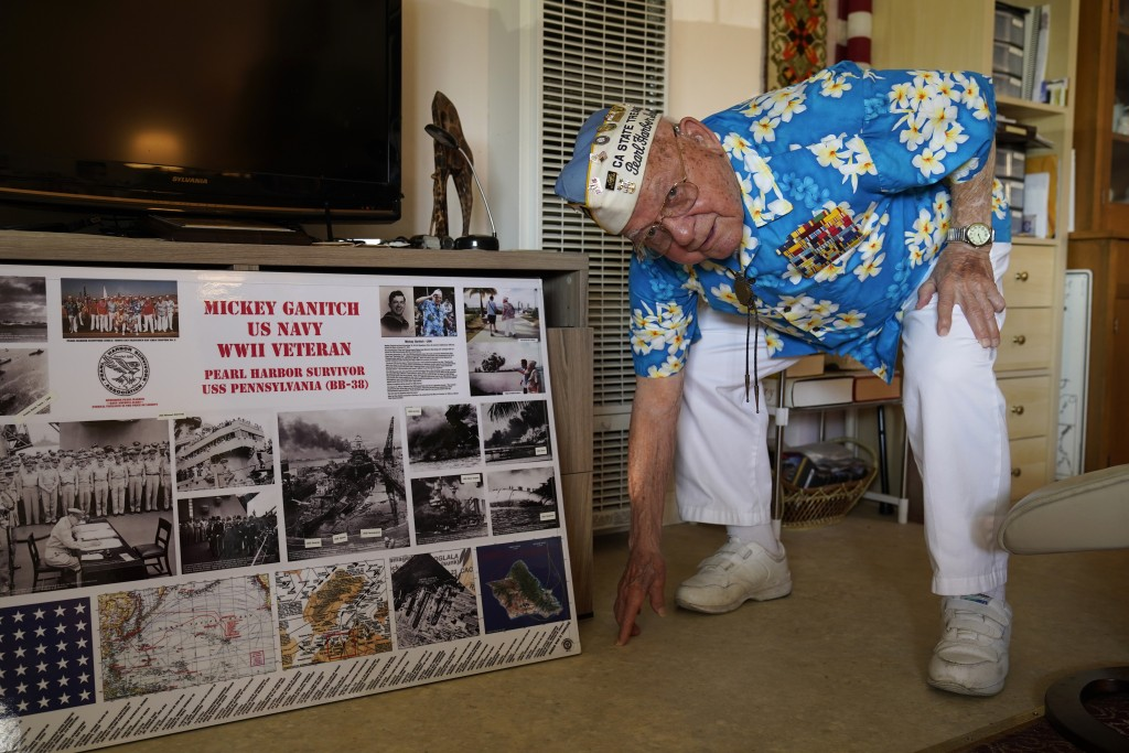 Mickey Ganitch, a 101-year-old survivor of the attack on Pearl Harbor, drops down to display his football stance in the living room of his home in San...