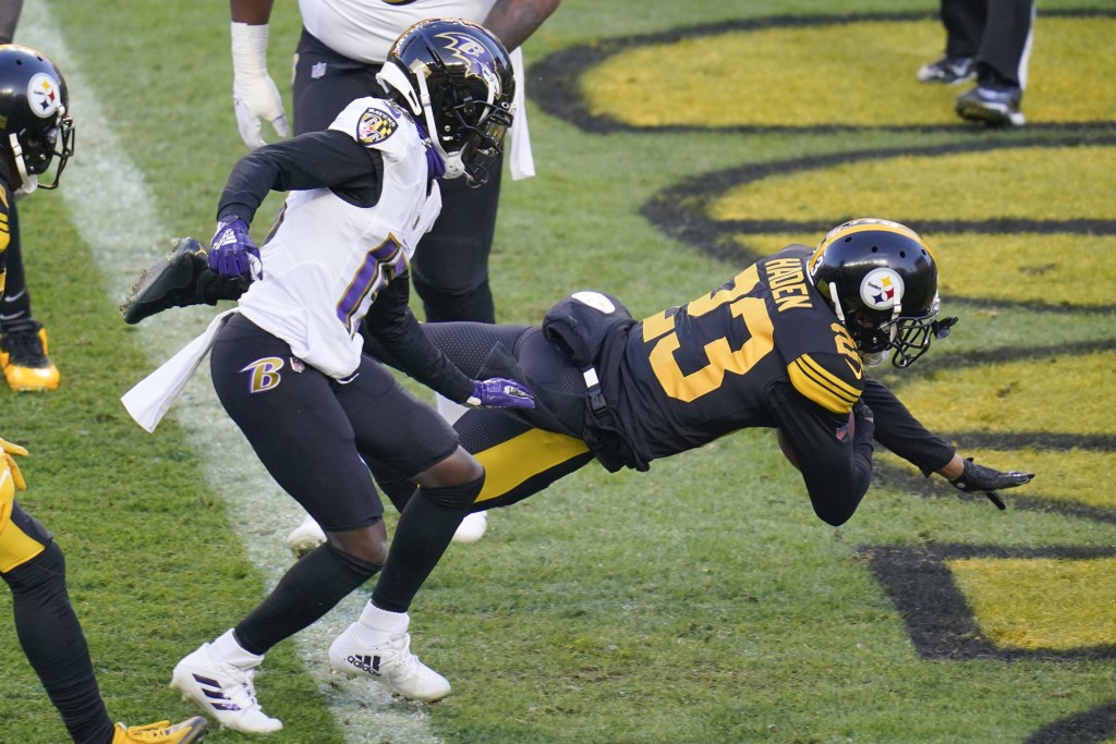 Pittsburgh Steelers cornerback Joe Haden (23) dives into the end zone with a touchdown in front of Baltimore Ravens wide receiver Marquise Brown (15) ...