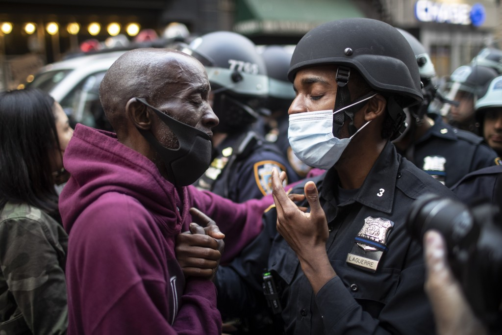 FILE - In this June 2, 2020 file photo, a protester and a police officer shake hands in the middle of a standoff at a rally in New York, calling for j...
