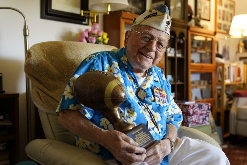 Mickey Ganitch, a 101-year-old survivor of the attack on Pearl Harbor, holds a football statue he was given, in the living room of his home in San Lea...