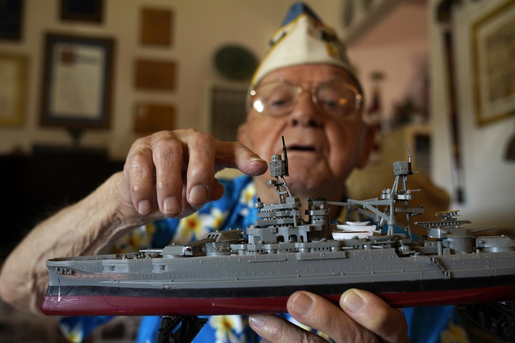 Mickey Ganitch holds up a model of the USS Pennsylvania and points to where he served as a lookout during the 1941 attack on Pearl Harbor, in the livi...