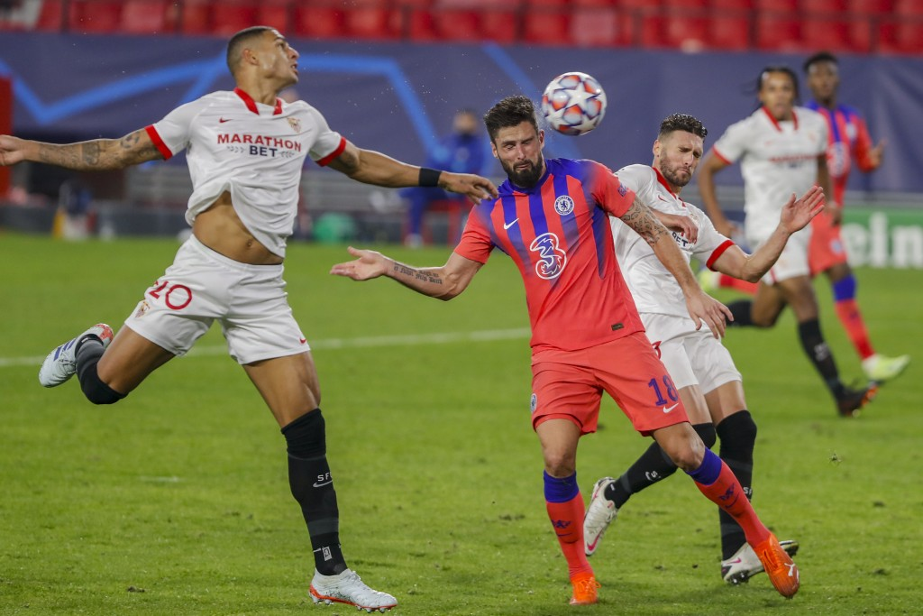 Chelsea's Olivier Giroud heads for the ball to score his side's third goal with teammates during the Champions League group E soccer match between Sev...