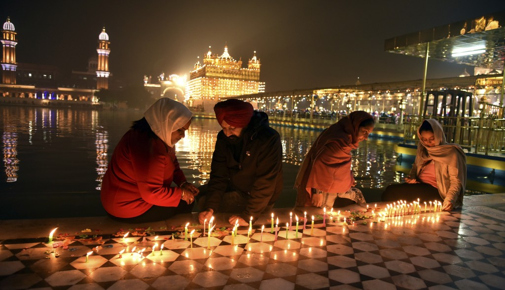 Sikh devotees light candlesin the pre-dawn hours at the illuminated Golden Temple, the holiest of Sikh shrines,during the birthanniversary of Guru ...