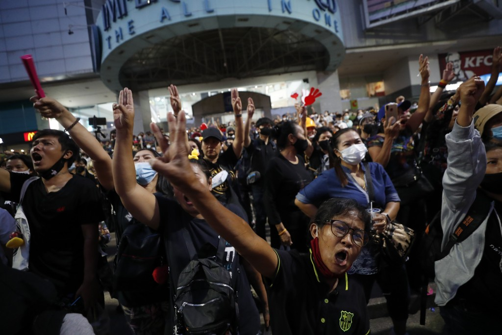 Protesters flash three-finger protest gestures as they gather to march in Bangkok, Thailand, Saturday, Nov. 28, 2020. Pro-democracy demonstrators are ...
