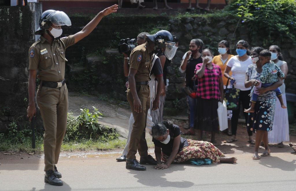 A family member of an inmate pleads lying at the feet of a policeman demanding to know the condition of her relative outside the Mahara prison complex...